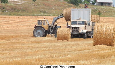 moving  bales of hay with  tractor