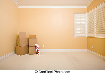 Moving Boxes and Sold Real Estate Sign on Floor in Empty...