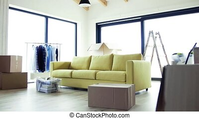 Moving boxes, sofa and clothes rack on the floor in new...