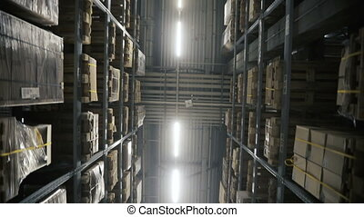 Camera moving between palettes with ordered goods and materials at warehouse. Multi level modern warehouse. Dolly shoot