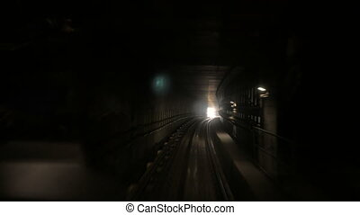 moving camera in dark railway tunnel toward bright light in the end