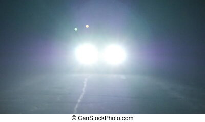 Moving car with lights at night. Car going on empty night road. In total darkness seen only the bright light of car headlights.
