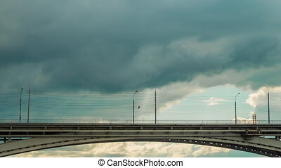 Moving cars and people on bridge against dramatic cloudy sky - timelapse