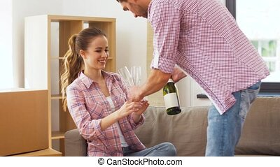 couple opening bottle of champagne at new home - moving,...