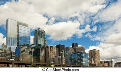 Moving clouds and sky over Seattle downtown cityscape with freeway auto traffic 4k uhd time lapse