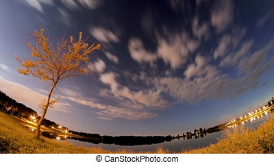 Moving clouds and stars above the lake at night, boomerang timelapse