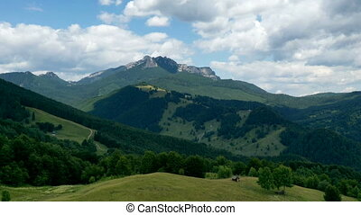 Moving clouds over rocky mountain, pasture and green forest ...