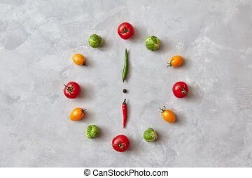 Moving colored vegetables make up a clock with moving arrows...