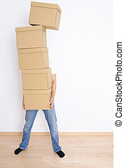Moving day - Young man carrying and dropping his stack of...