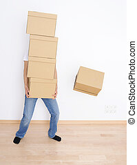 Moving day - Young man carrying and dropping his stack of ...