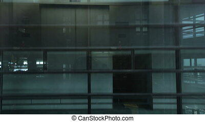 Moving elevator in modern office business building looking out of glass windows showing interior of floors in the building.