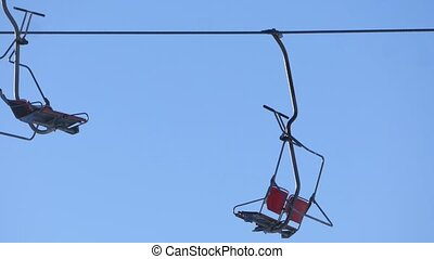 Moving empty chairlifts on the blue sky background