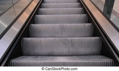 Moving escalator stairs in shopping mall. Close up view.