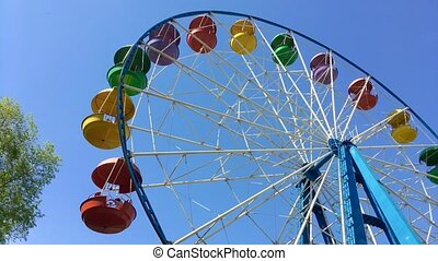 Moving ferris wheel on the blue sky background.