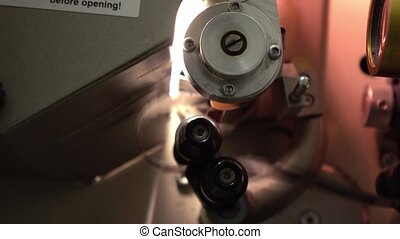 Moving film in professional 35 mm film cinema projector, 4K video, part of set