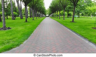 Moving forward on a cobblestone walkway in a park. Well-groomed green grass and trees.