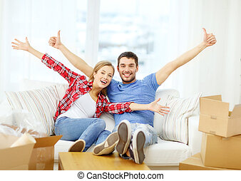 smiling couple relaxing on sofa in new home