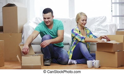 smiling couple unpacking boxes with kitchenware - moving,...