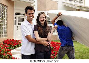 Real estate and moving home: Couple showing keys and relocator carrying mattress into their new home
