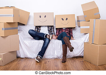 Moving home - Couple with cardboard boxes on their heads...