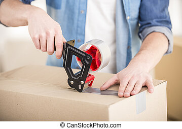 Moving home - Close-up. Man packing boxes. Moving, purchase...