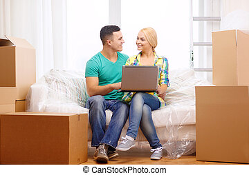 couple relaxing on sofa with laptop in new home