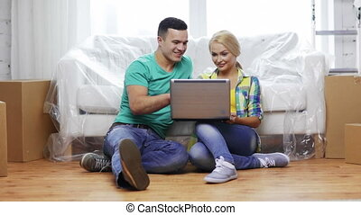 couple with laptop sitting on floor in new house