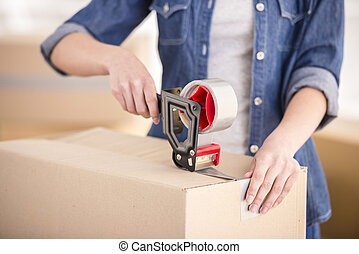 Moving home - The young happy woman packing boxes. Moving, ...