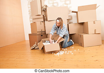 Moving house: Happy woman unpacking box in new home, kitchen...