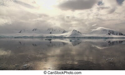 Moving Ice Floes and Ice Sheets in the calm Antarctic Sea, Reflection of Antarctica Mountain in water surface. Amazing beautiful views of Nature and landscape of snow, ice and white of Antarctic.