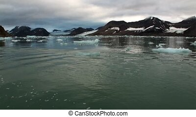 Moving Ice Floes on background of mountain on water of...