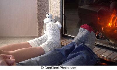 Moving legs in woolen socks heat up near fireplace