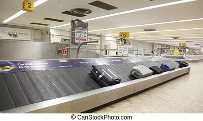 Moving luggage belf with bags in airport in London, UK. -...