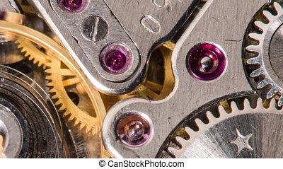 Moving metal gears inside working watch mechanism