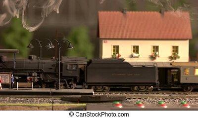 Moving model of steam locomotive. Model railroading passenger station.