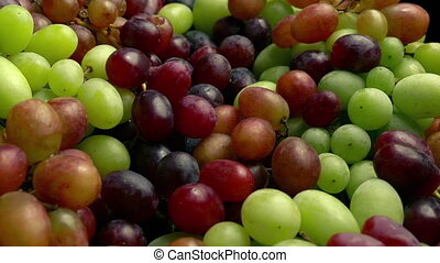 Dolly shot moving over pile of red and green grapes