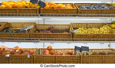 Moving past fresh fruits in a supermarket grocery. Shelves at the shop. Close up