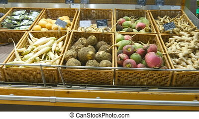 Moving past fresh vegetables in a supermarket. Grocery...