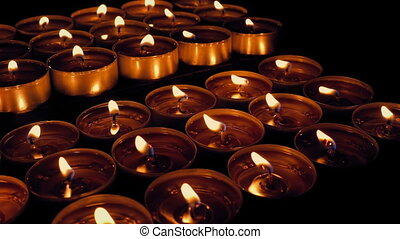 Passing rows of tea candles in the dark