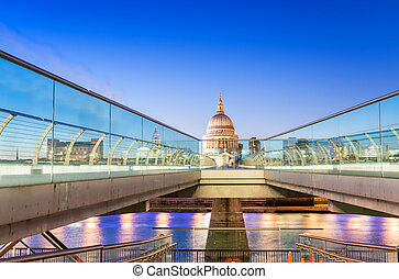 Moving people alonf Millennium Bridge in London. Night view of St Paul Cathedral