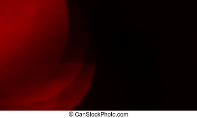 Moving red defocused lights through dark background.