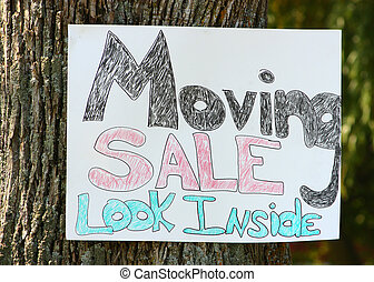 Moving Sale Sign - A sign tacked on a tree, announcing a...