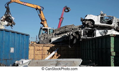 Moving Scrap Metal - Cranes with hydraulic gripper moving...