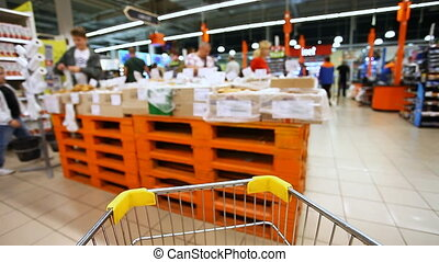 moving shopping cart in a large supermarket , blurred, abstract
