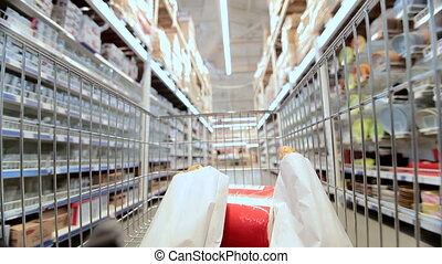 shopping cart in supermarket - Moving shopping cart in...