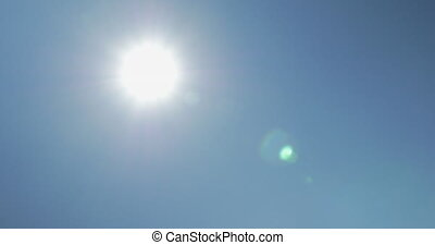 Moving shot from sun to solar panels against blue clear sky