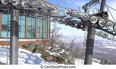 Moving ski chair lift station on mountain top in a sunny winter day