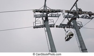 Moving ski chair lift station on mountain top in cloudy winter day