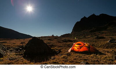 Moving stars above tent at night time lapse