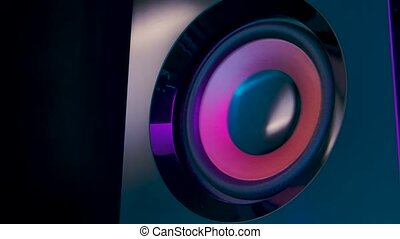 Moving subwoofer close up. Speaker part. Black membrane lit by colorful neon club lights. Concept of musical instrument. Close up. Slow motion